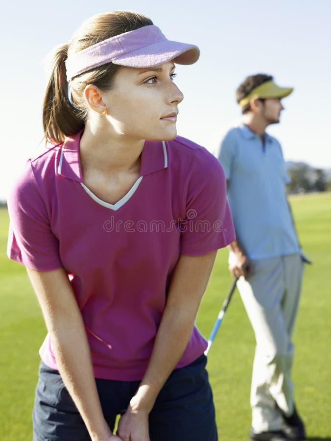 打与男性朋友的妇女高尔夫球 免版税库存图片