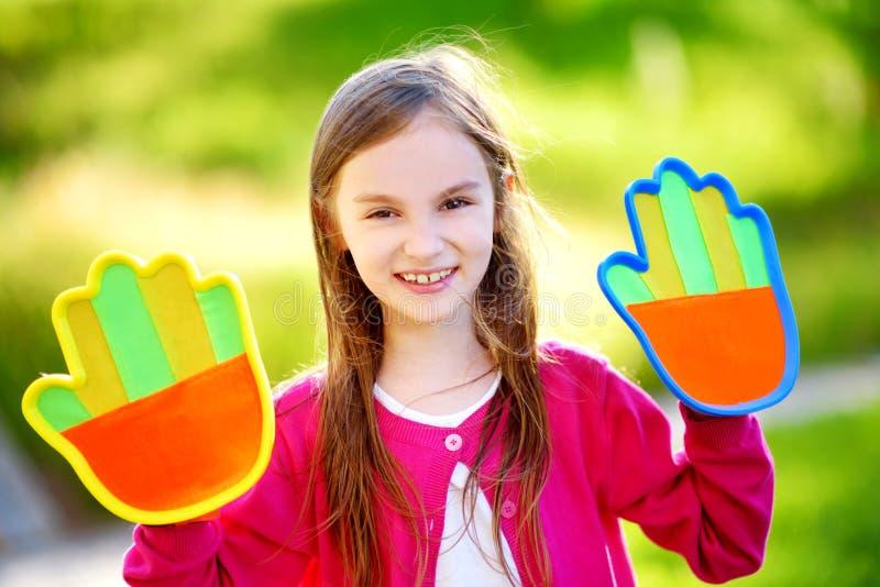 打与稠粘的维可牢尼龙搭扣棕榈垫的逗人喜爱的小女孩一场球传染性的比赛 免版税图库摄影