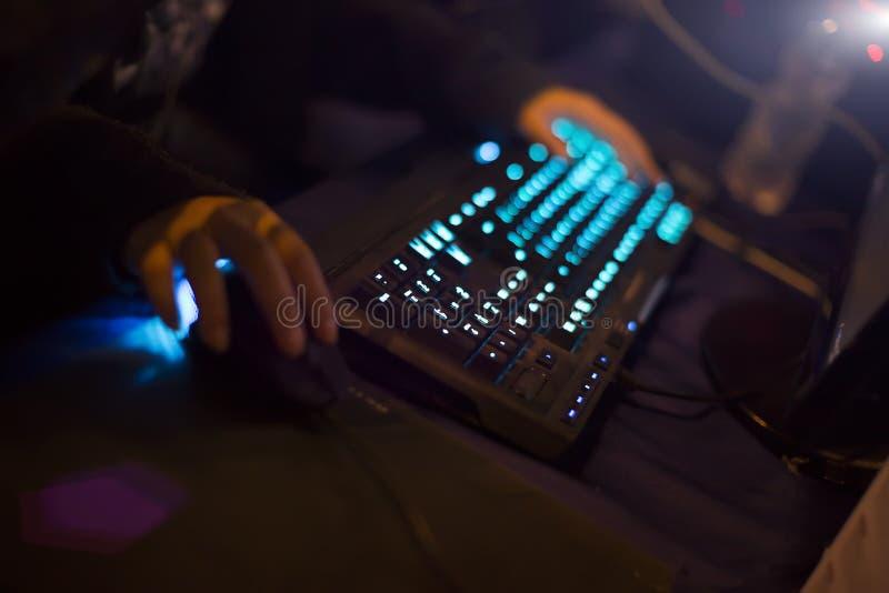 打与膝上型计算机的年轻人电子游戏 有计算机的游戏玩家在黑暗或后在晚上 在老鼠和键盘的手 免版税库存照片
