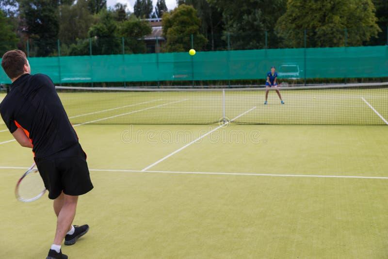 打与他的女性伙伴的年轻人网球 免版税库存照片