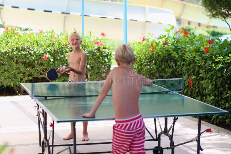 打乒乓球的两个愉快的男孩户外 免版税图库摄影