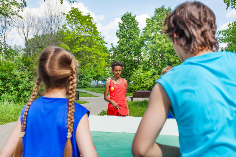 打乒乓球的四个少年朋友外面 免版税库存照片