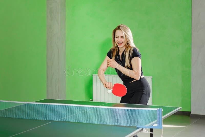 打乒乓球的少女 运动员踢与网球拍的球 免版税库存图片