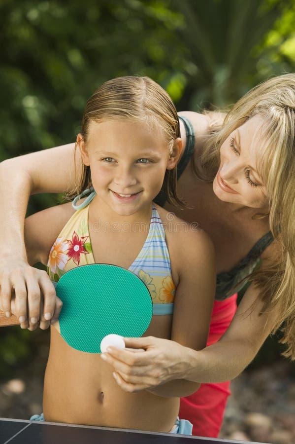 打乒乓球的母亲教的女儿 库存照片