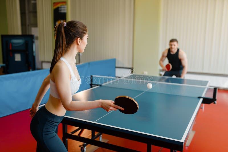 打乒乓球的男人和妇女户内 图库摄影