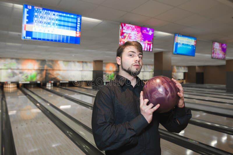 打保龄球的商人 一个人的画象有一个球的在他的以轨道为背景的手上滚保龄球的 免版税库存图片
