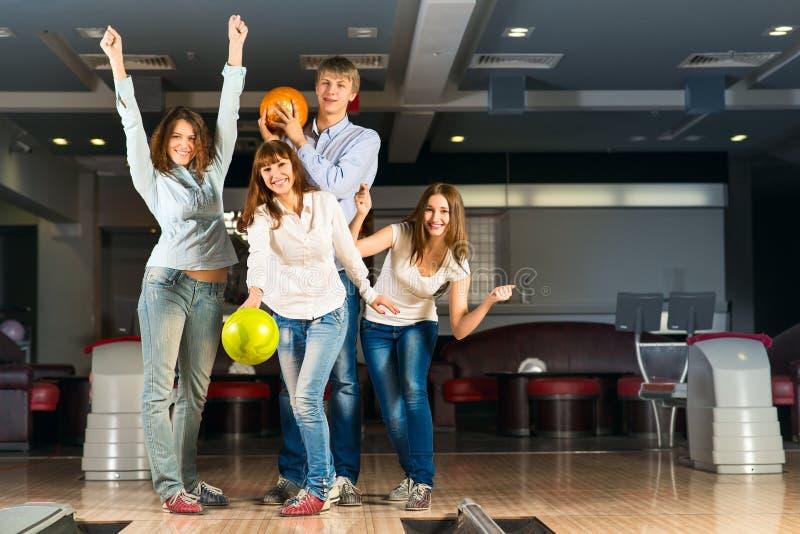 打保龄球的小组年轻朋友 免版税库存图片