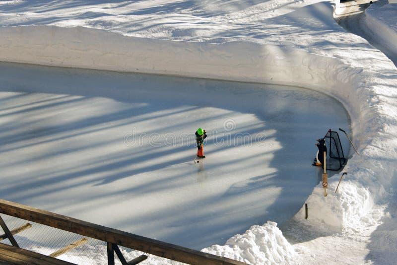 打冰球的孩子在阿尔卑斯瑞士在冬天 免版税图库摄影