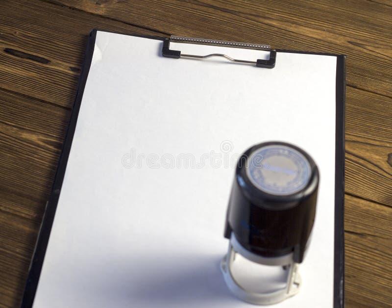 打印在一个空白纸,木背景印刷品 免版税库存图片