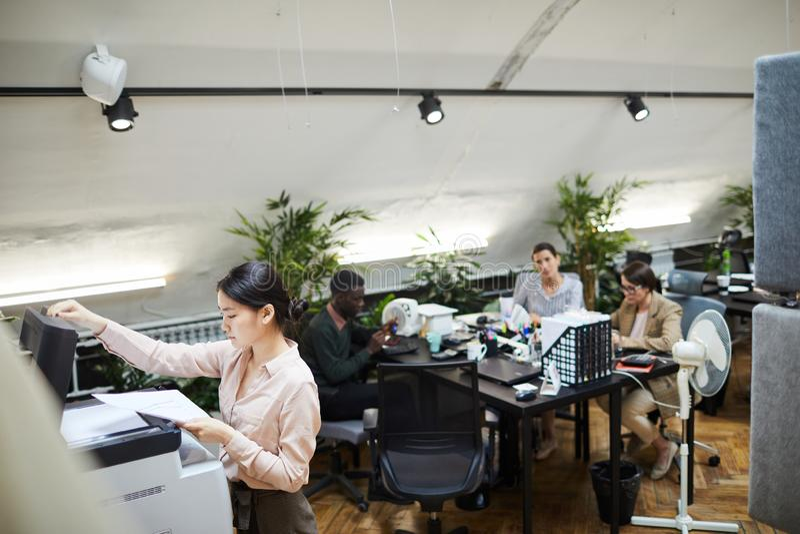 打印文件的年轻女实业家在办公室 免版税库存图片