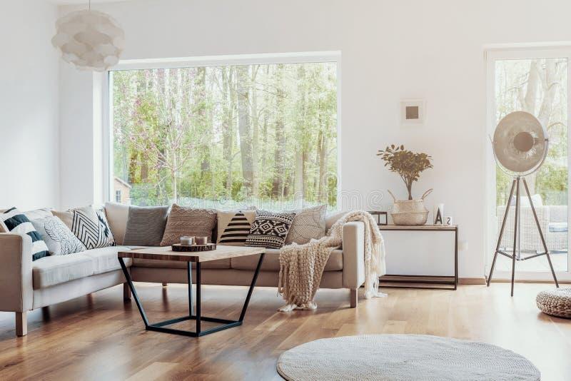 打印样式枕头在一个米黄壁角沙发由一个大玻璃窗在与白色墙壁的温暖的客厅内部 免版税库存照片