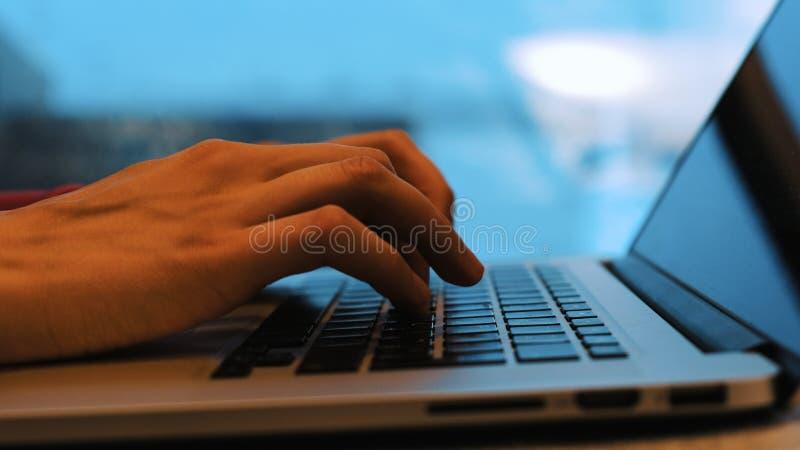 打印输入机场的自由职业者妇女在膝上型计算机键盘特写镜头,手在一间候诊室 浮动焦点 免版税库存照片