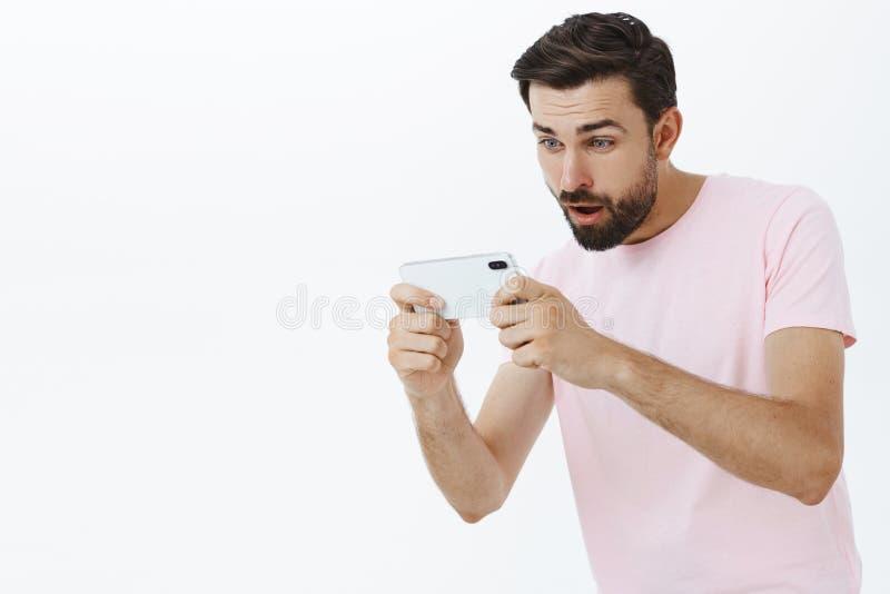 打可笑的比赛的成人有胡子的人通过拿着手机用两只手的智能手机看起来聚焦和激发 库存图片