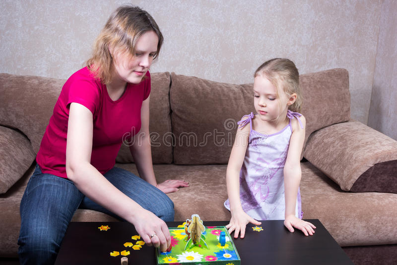 打台式游戏机的妈妈和女儿 库存图片