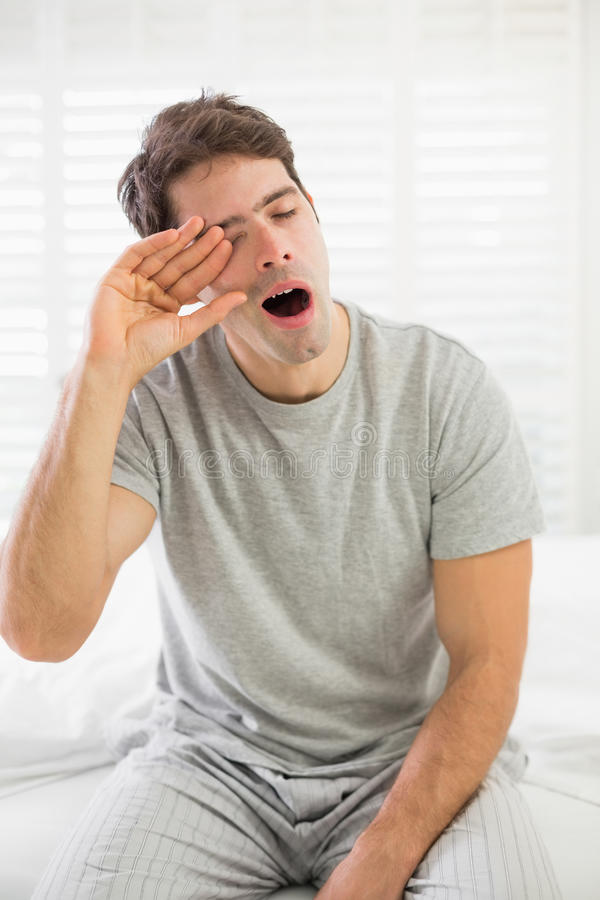 打呵欠困的人,他在床上摩擦他的眼睛 库存图片