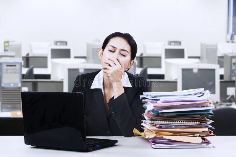 打呵欠在办公室的被用尽的女实业家 免版税库存图片