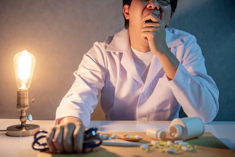 打呵欠在医院诊所的劳累过度的医生 库存照片