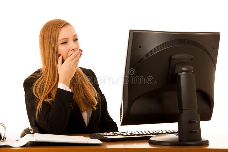 打呵欠在工作的美丽的youn g女商人在办公室- exau 免版税库存图片