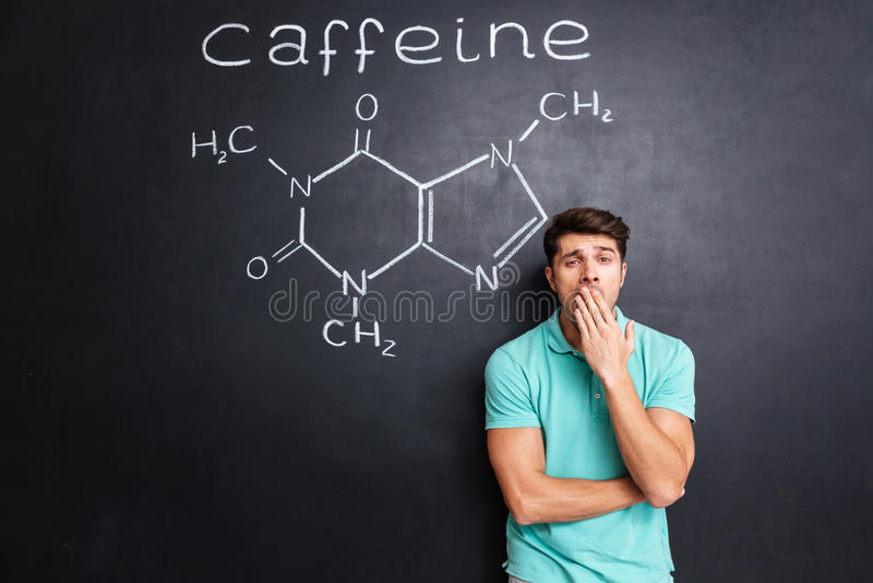 打呵欠在有拉长的咖啡因分子的黑板的疲乏的困人 库存照片