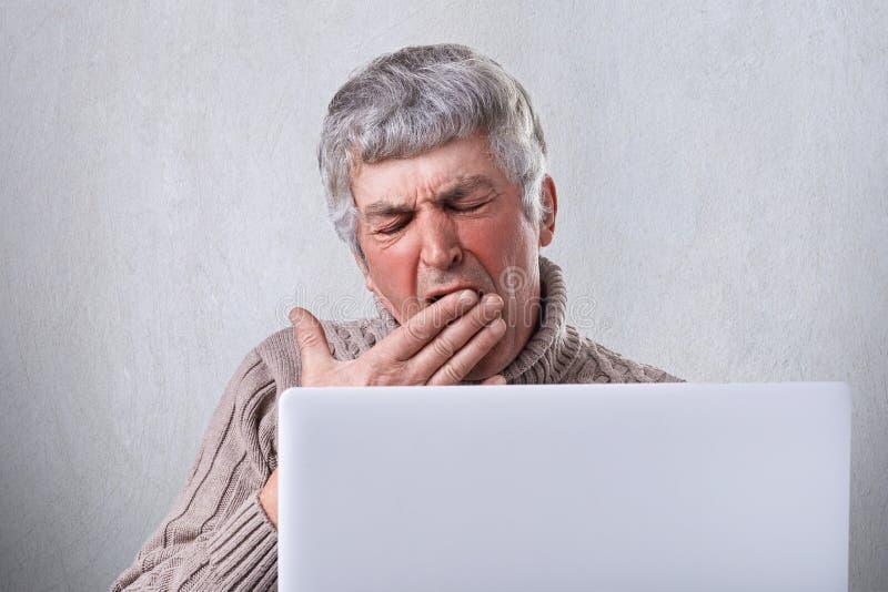 打呵欠在被疲劳的他的膝上型计算机frot的一个疲乏的老人,当时在写他的书以后 有举行他的灰色头发的一个成熟人 库存图片