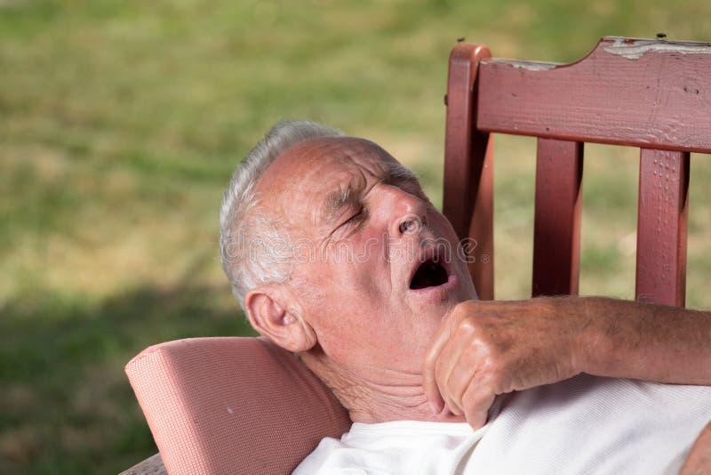 打呵欠在长凳的庭院里的老人 免版税库存照片