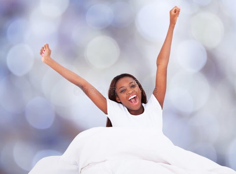打呵欠的妇女,当舒展在床上时 免版税库存照片