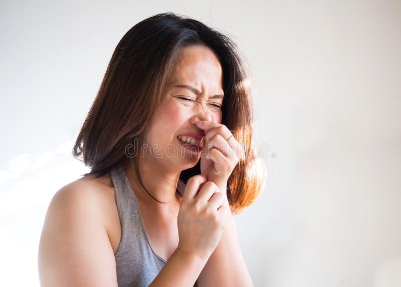 打喷嚏中间成人亚裔的妇女和紧压鼻子的用途手 P 免版税库存照片