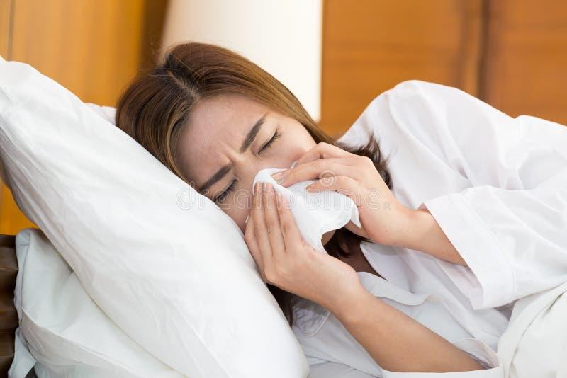 打喷嚏在床上的一个组织的亚裔妇女