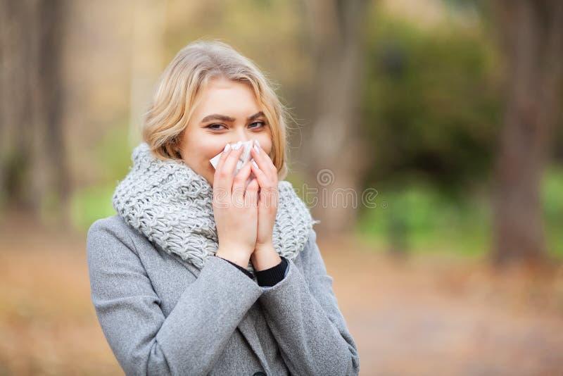 打喷嚏在组织的女孩 吹她的在公园的年轻女人鼻子 妇女画象室外打喷嚏,因为寒冷和流感 免版税库存照片