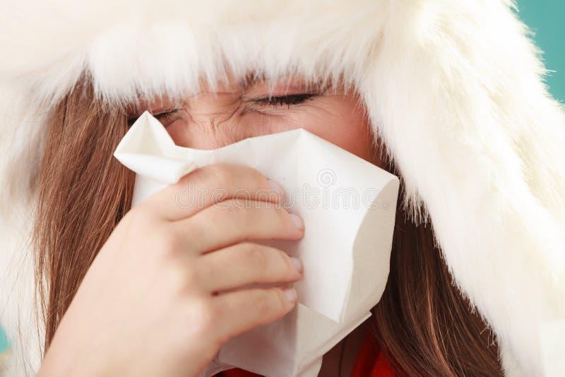 打喷嚏在组织的病的妇女 冬天寒冷 免版税库存照片