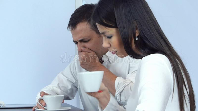 打喷嚏病的年轻的人,当检查他的头热病和给他餐巾时的担心的女性 图库摄影