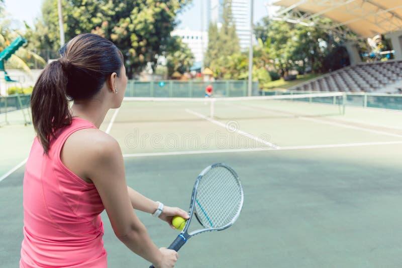 打在一个专业法院的适合少妇的背面图网球 库存照片