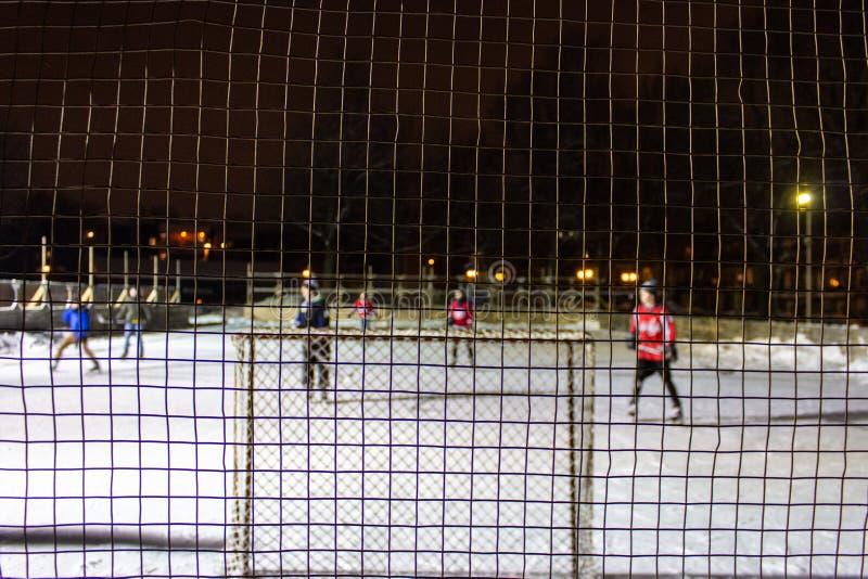 打在冰的孩子室外曲棍球在晚上在魁北克,加拿大- 1/3的公园 免版税图库摄影