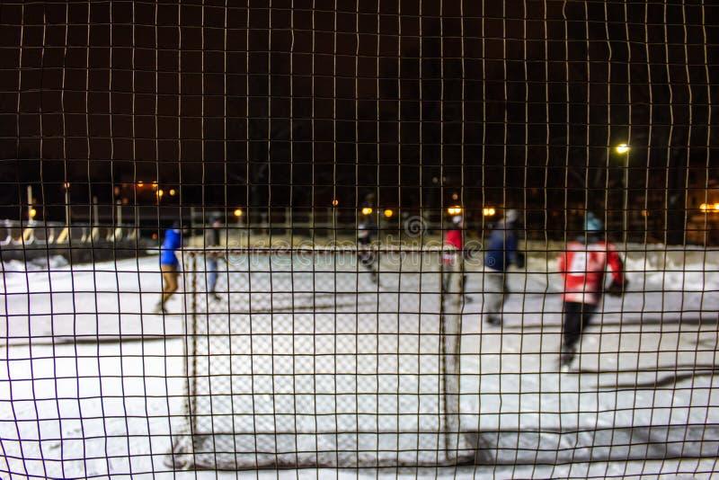 打在冰的孩子室外曲棍球在晚上在魁北克,加拿大- 3/3的公园 免版税库存图片
