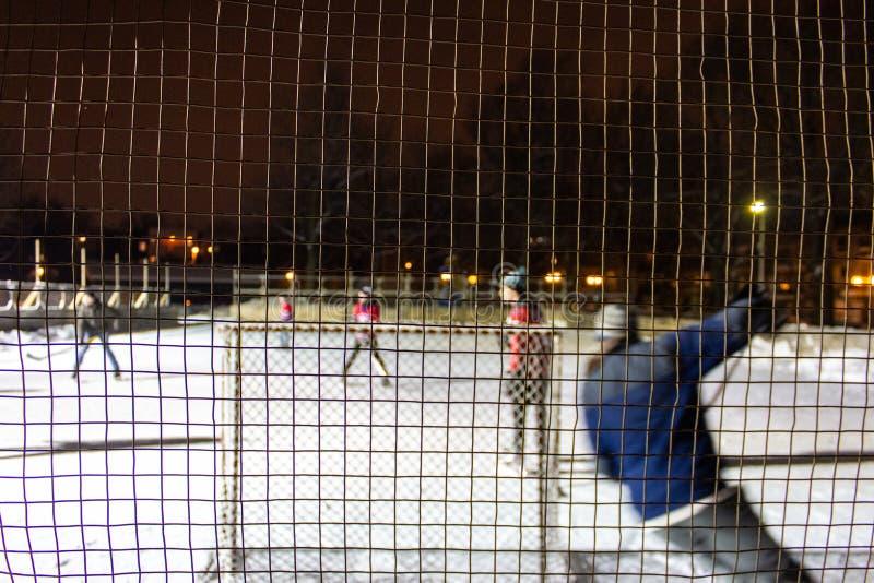 打在冰的孩子室外曲棍球在晚上在魁北克,加拿大- 2/3的公园 库存照片