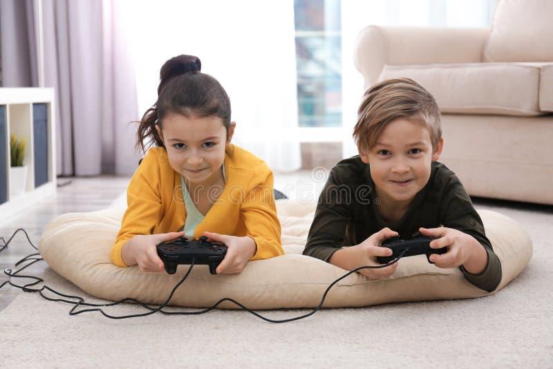 打在地板上的逗人喜爱的孩子电子游戏 库存照片