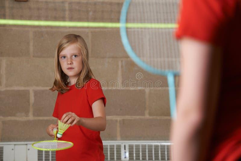 打在学校健身房的两个女孩羽毛球 免版税库存图片