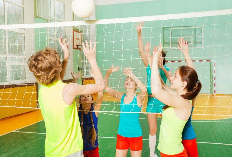 打在学校健身房的少年排球 免版税库存照片