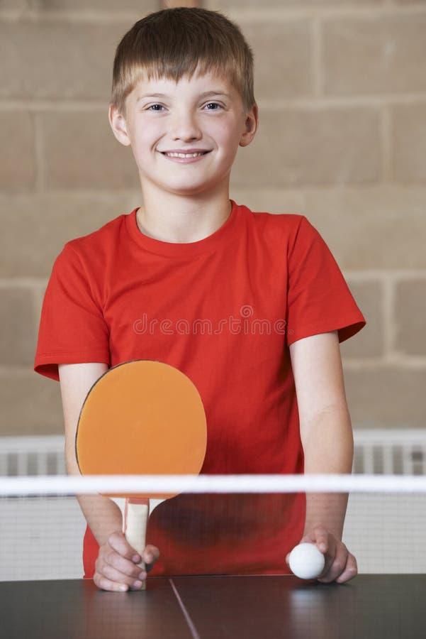 打在学校健身房的男孩画象乒乓球 免版税图库摄影