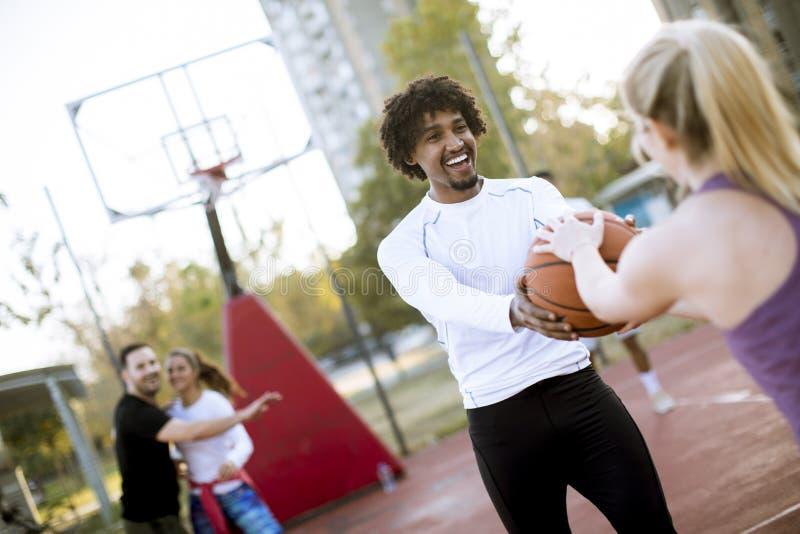 打在室外法院的多种族夫妇篮球 免版税库存图片