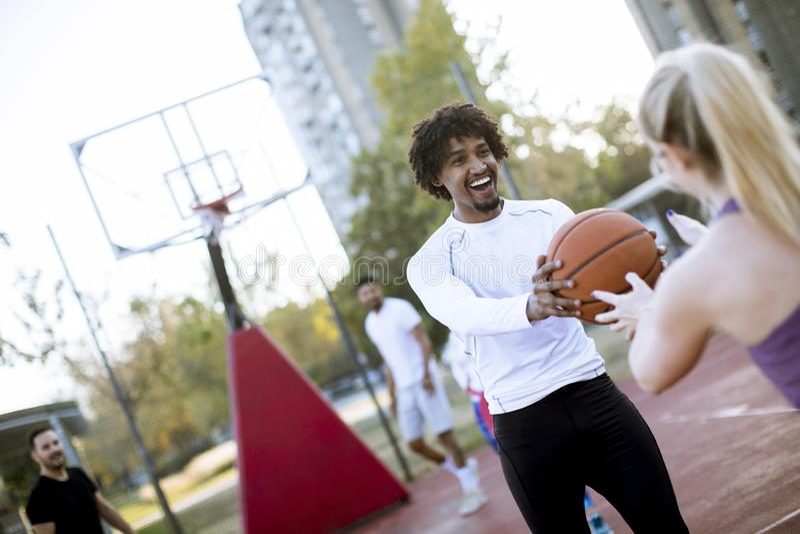 打在室外法院的多种族夫妇篮球outumn天 免版税库存照片