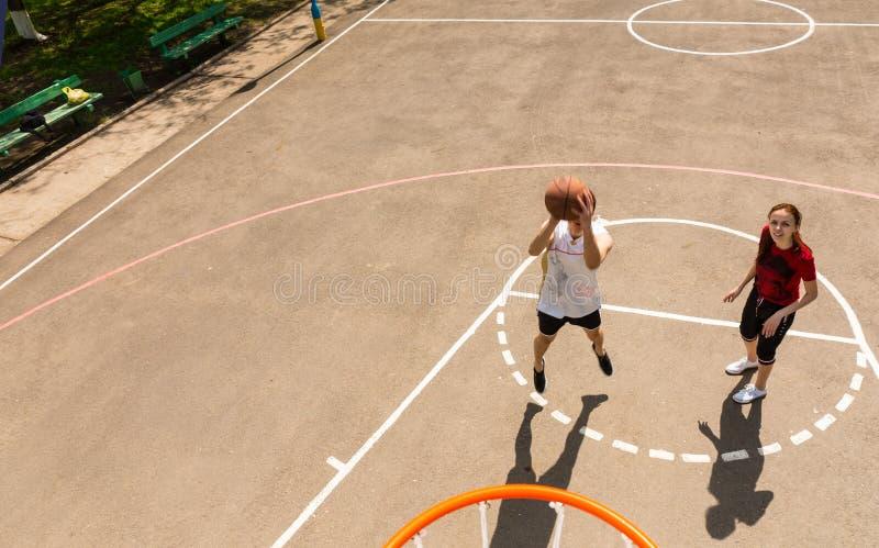 打在室外法院的夫妇篮球 库存照片