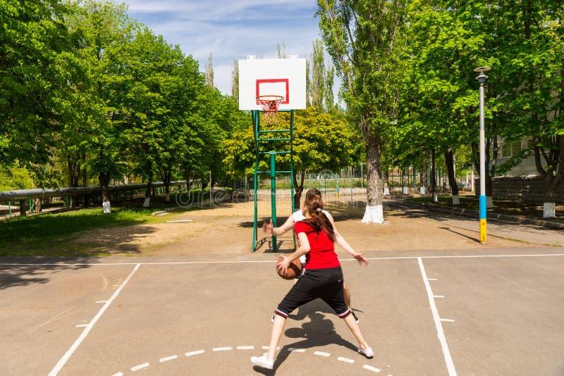 打在室外法院的夫妇篮球 免版税库存图片