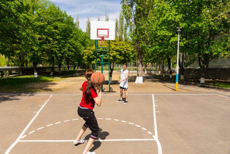 打在室外法院的夫妇篮球 免版税图库摄影