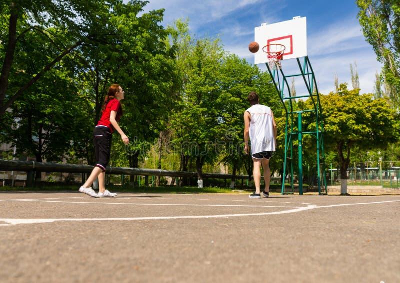 打在室外法院的夫妇篮球 库存图片