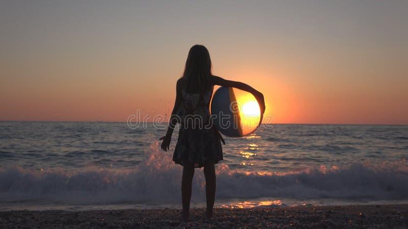 打在日落的孩子海滩球,孩子观看的海波浪,在日落的女孩景色 免版税图库摄影