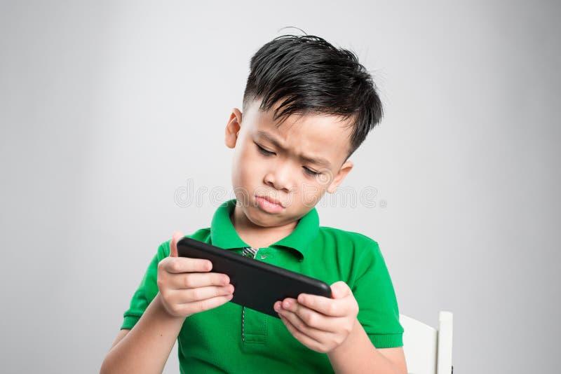 打在智能手机的一个发笑逗人喜爱的小孩的画象比赛被隔绝在灰色背景 免版税库存图片