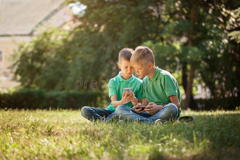 打在智能手机的两个小弟弟比赛以兴奋,当坐草在公园时 免版税图库摄影