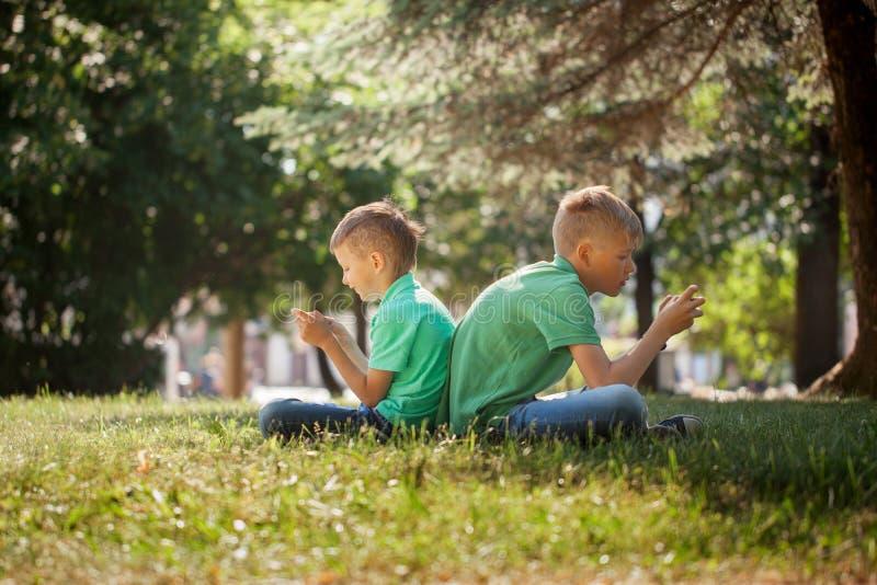打在智能手机的两个小弟弟比赛以兴奋,当坐草在公园时 图库摄影