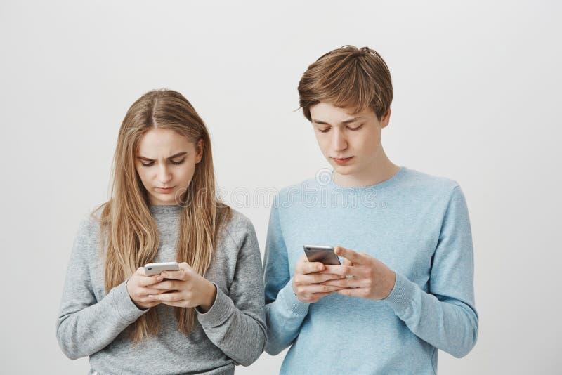 打在智能手机的兄弟姐妹比赛,挑战互相 被聚焦的漂亮的女人和人演播室射击  免版税库存照片